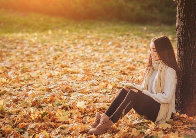 Schöner junger brunette, der auf einem gefallenen herbstlaub in einem park sitzt, ein buch liest oder ein tagebuch schreibt