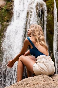 Schöner junger erwachsener am wasserfall