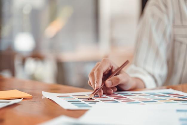 Schöner junger freiberuflicher grafikdesigner, der farbmuster für das entwerfen des bildschirmplans der mobilen anwendung im modernen büro wählt.