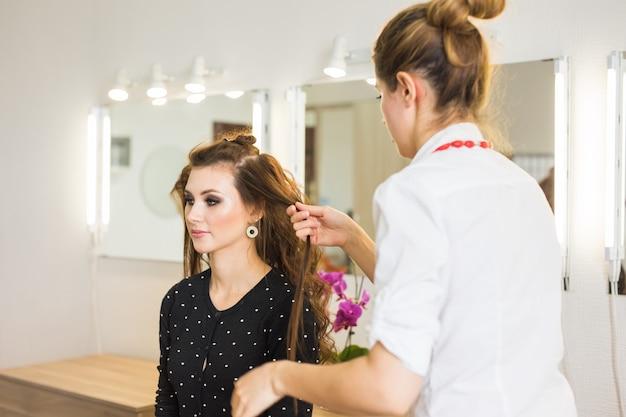 Schöner junger friseur, der weiblichen kunden im wohnzimmer einen neuen haarschnitt gibt.