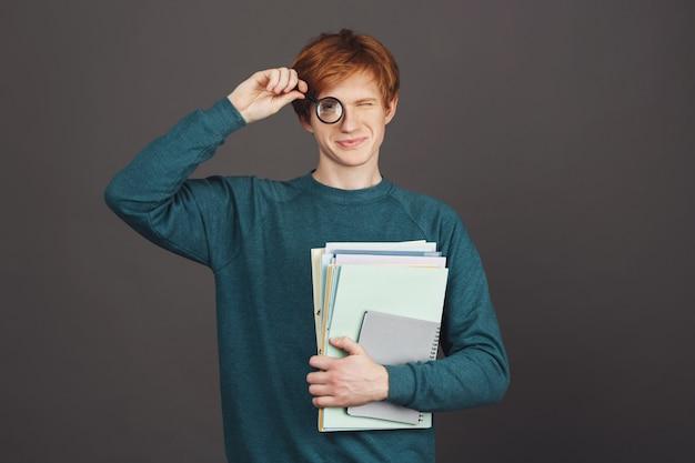 Schöner junger fröhlicher männlicher student im stilvollen grünen pullover, der lupe vor auge und viele notizbücher hält, mit glücklichem und entspanntem ausdruck. schwarze wand