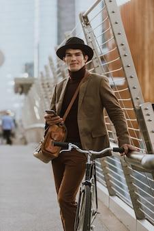 Schöner junger geschäftsmann mit seinem modernen fahrrad.