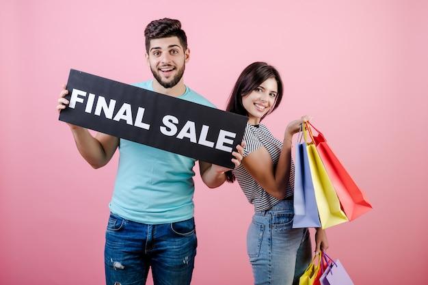 Schöner junger glücklicher lächelnder paarmann und -frau mit abschließendem verkaufszeichen und bunten einkaufstaschen