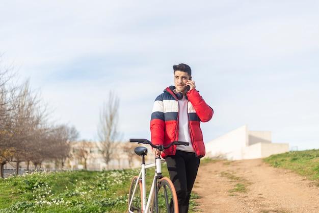 Schöner junger hipster-mann, der eine radtour genießt und ein smartphone beim gehen auf park verwendet