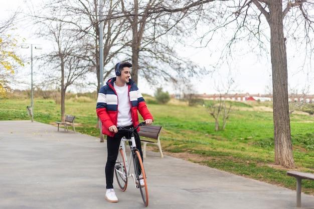 Schöner junger hipster-mann, der eine radtour genießt und ein smartphone benutzt, während musik durch kopfhörer hört