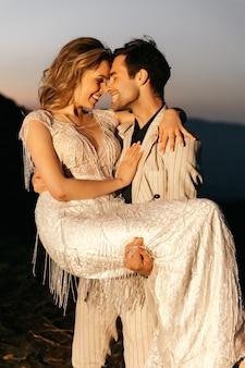 Schöner junger hochzeitspaar lächelnder bräutigam, der die braut in seinen armen hält