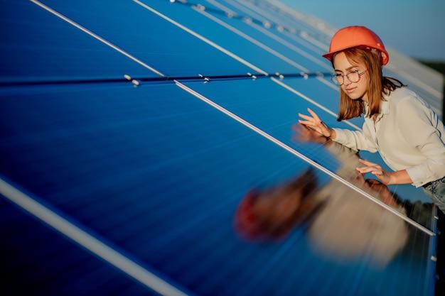 Schöner junger ingenieur, der nahe sonnenkollektoren im freien steht, green energy concept.