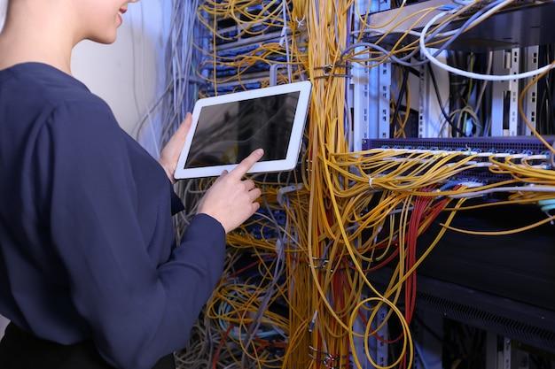 Schöner junger ingenieur mit tablet-computer im serverraum