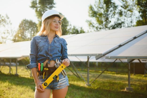 Schöner junger ingenieur nahe sonnenkollektoren im freien