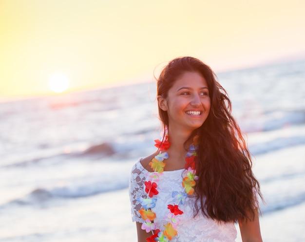 Schöner junger jugendlicher mit einem weißen kleid auf dem strand am sonnenuntergang