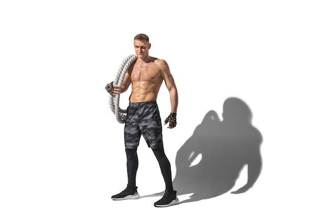 Schöner junger männlicher athlet, der auf weiß mit schatten übt