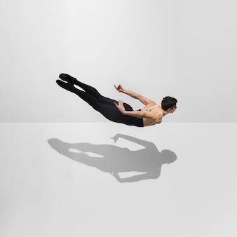 Schöner junger männlicher athlet, der auf weißem studio mit schatten im sprung, luftfliegen übt