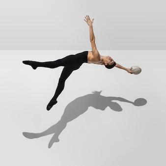 Schöner junger männlicher athlet, der auf weißem studiohintergrund mit schatten im sprung, luftfliegen übt