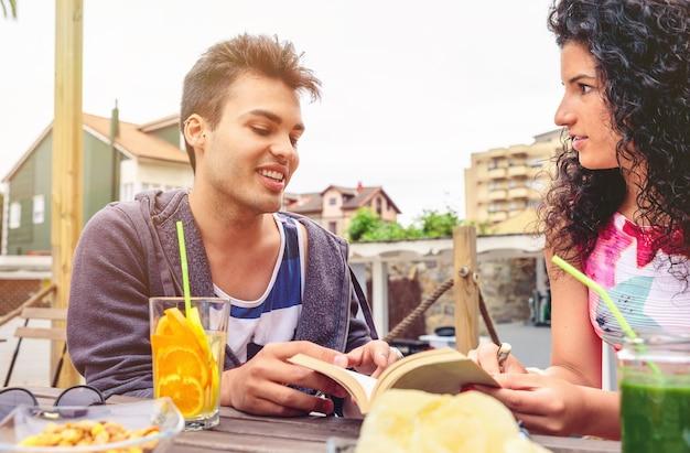 Schöner junger mann, der an einem freien sommertag im freien mit einem freund am tisch mit gesunden getränken spricht