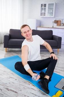 Schöner junger mann, der auf dem boden sitzt und eine flasche wasser hält, während er online trainiert