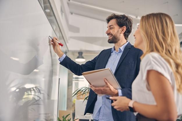 Schöner junger mann, der auf whiteboard schreibt und lächelt, während er neben einer kollegin steht