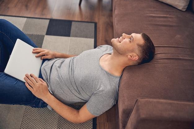 Schöner junger mann, der mit seinem laptop auf den knien in der nähe der couch liegt, während er träumt und lächelt