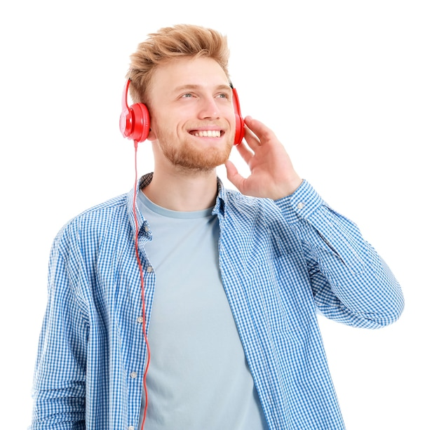 Schöner junger mann, der musik auf weißem hintergrund hört listening