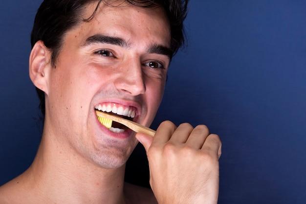 Schöner junger mann, der seine zähne putzt