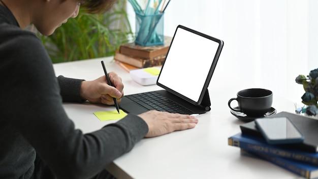 Schöner junger mann der seitenansicht, der computertablett verwendet und notiz auf notizbuch macht.
