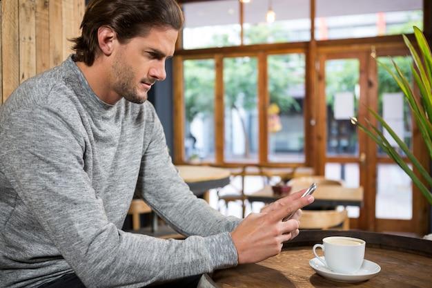 Schöner junger mann, der smartphone am tisch im kaffeehaus verwendet