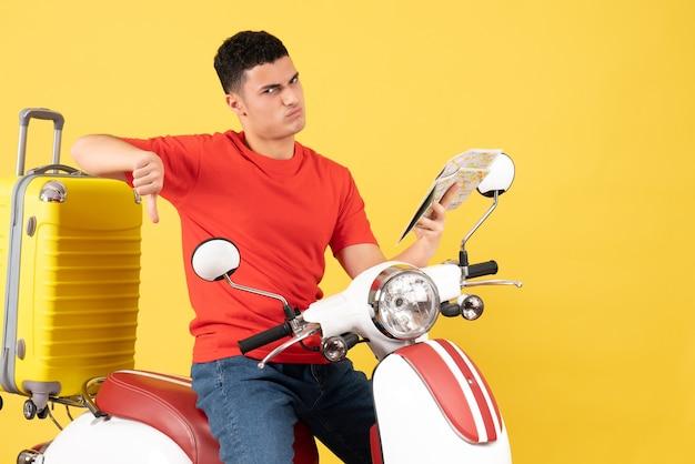 Schöner junger mann der vorderansicht auf moped, der daumen unten hält karte hält