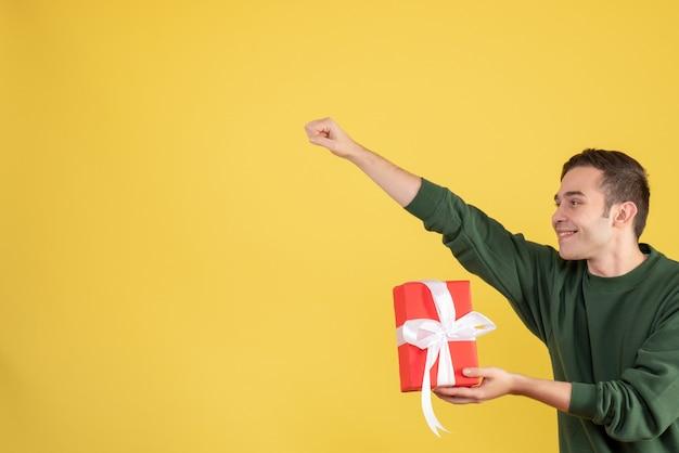 Schöner junger mann der vorderansicht, der das geschenk hält, das superheldengeste auf gelb aking
