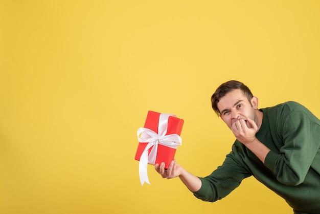 Schöner junger mann der vorderansicht, der geschenk auf gelb hält