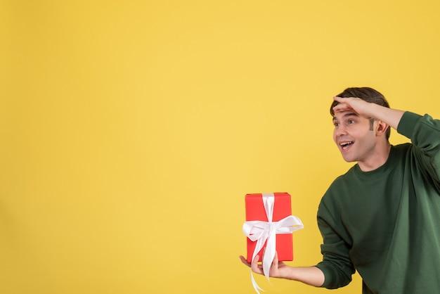 Schöner junger mann der vorderansicht, der geschenk betrachtet, das etwas auf gelb betrachtet