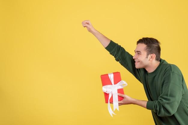 Schöner junger mann der vorderansicht, der geschenk hält, das superheldengeste auf gelb macht
