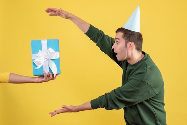 Schöner junger mann der vorderansicht, der geschenk von menschlicher hand auf gelb nimmt
