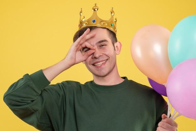 Schöner junger mann der vorderansicht mit der krone, die ballons hält, die okey zeichen vor auge auf gelb setzen