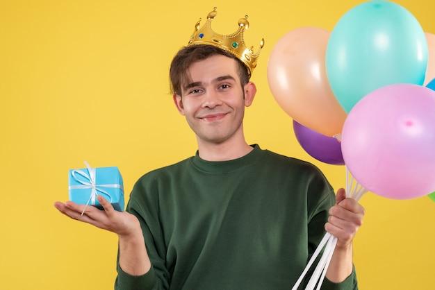 Schöner junger mann der vorderansicht mit der krone, die luftballons und blaue geschenkbox auf gelb hält