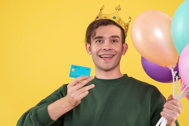 Schöner junger mann der vorderansicht mit krone, die luftballons und karte auf gelb hält