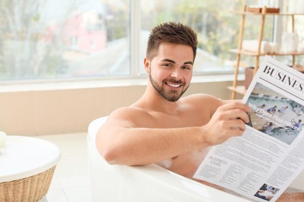 Schöner junger mann, der zeitung liest, während er zu hause badet