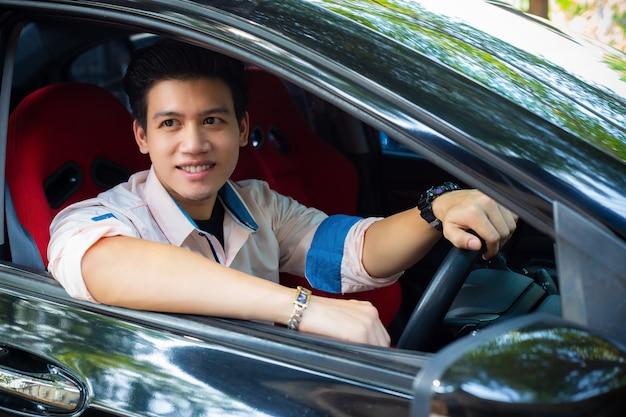 Schöner junger mann im schwarzen auto