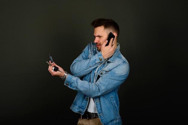 Schöner junger mann in einer intelligenten freizeitkleidung, der ein smartphone hält und mit einem lächeln in die kamera schaut