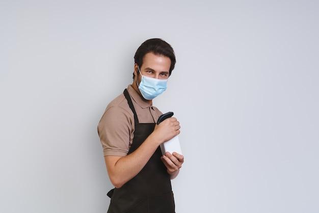 Schöner junger mann in schürze, der einen schützenden gesichtsschutz trägt und im stehen reinigungsspray hält...