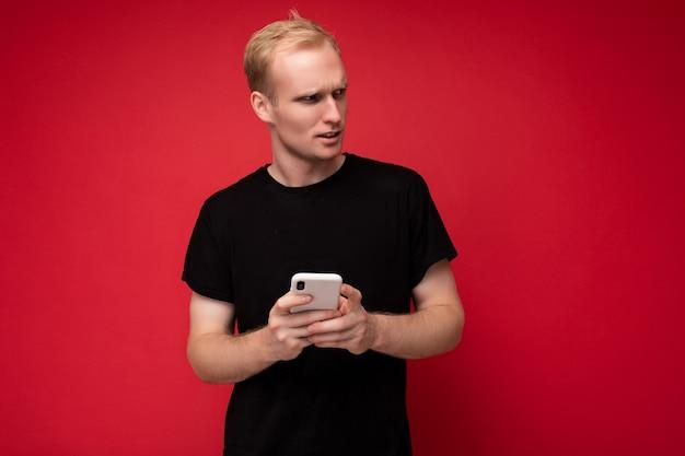 Schöner junger mann isoliert über der hintergrundwand, der alltagskleidung trägt und handy-schreib-sms mit blick auf die seite verwendet.