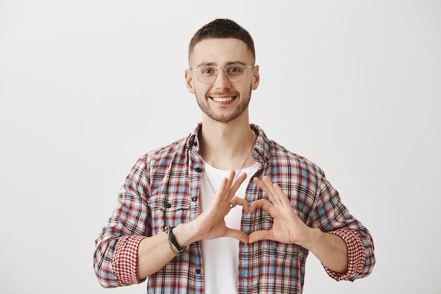 Schöner junger mann mit brille posiert