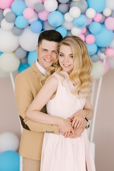 Schöner junger mann mit einem wunderschönen blonden mädchen, das auf dem hintergrund der weißen und rosa luftballons umarmt und lächelt.