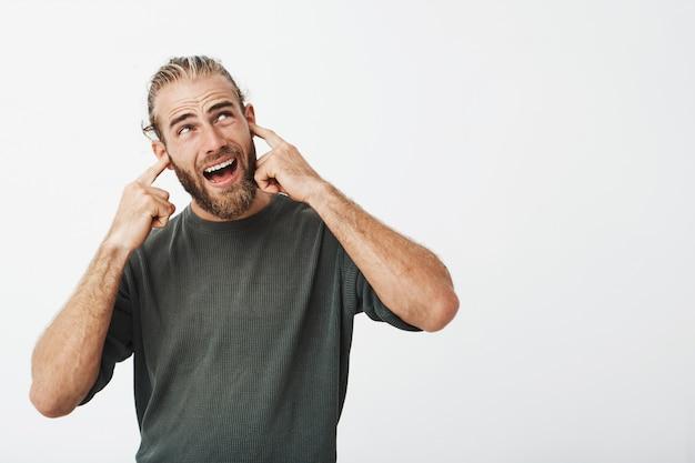 Schöner junger mann mit stilvollem haarschnitt und bart, der ohren mit den fingern verstopft