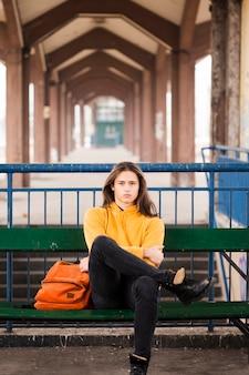 Schöner junger mann sitzt auf einer bank