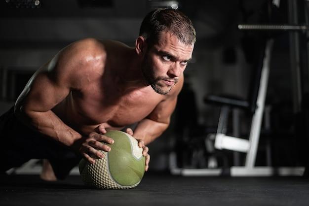 Schöner junger muskulöser mann, der gymnastik in der turnhalle mit ball tut