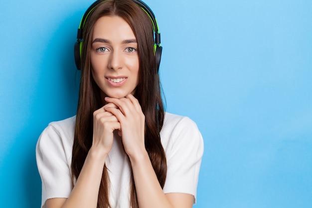 Schöner junger sexy mädchen-dj, der musik in den grünen kopfhörern auf einem blau hört