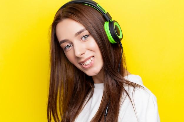Schöner junger sexy mädchen-dj, der musik in den grünen kopfhörern auf einem gelben hört