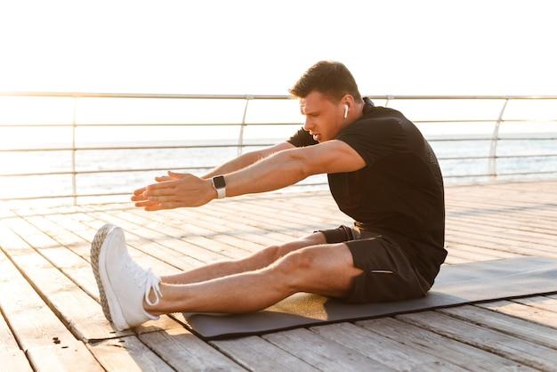 Schöner junger sportler machen übungen auf sportteppich, der musik hört.