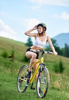 Schöner junger sportler weiblicher fahrer, der auf gelbem fahrrad auf einem ländlichen weg in den bergen radelt und talblick genießt. outdoor-sportaktivität lifestyle-konzept