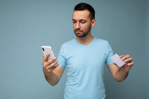 Schöner junger unrasierter brünetter mann mit bart, der alltägliches blaues t-shirt isoliert trägt