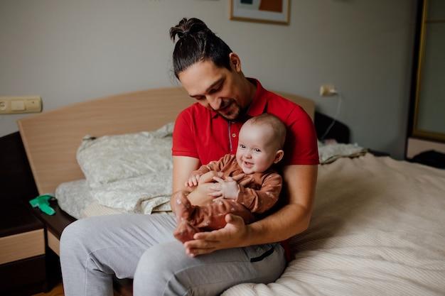 Schöner junger vater mit baby in den armen das konzept einer glücklichen familienvaterschaft